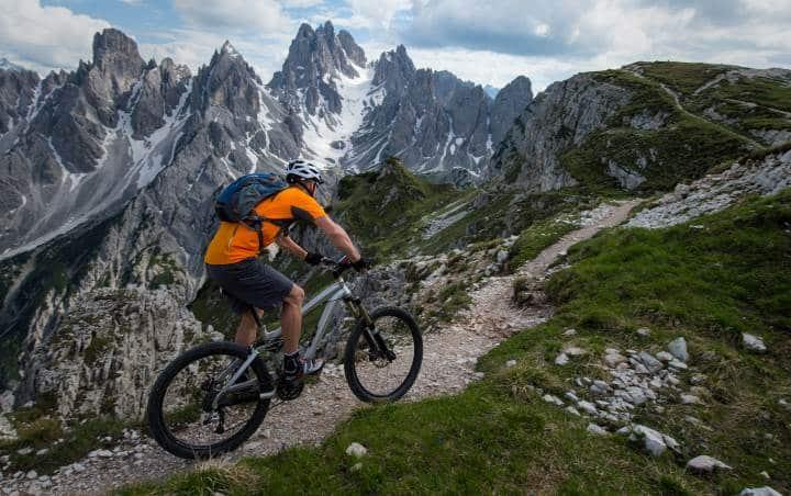 man track riding through mountain range
