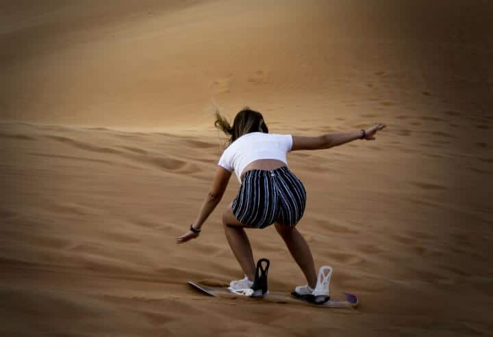 Lady dune surfing and wearing smartwatch