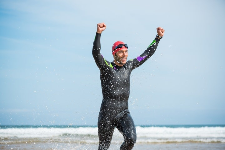 man with swimming watch celebrating open swim
