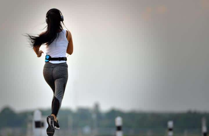 Woman running and tracking fitness