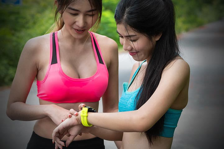 Two female runners stopped to check their smartwatch