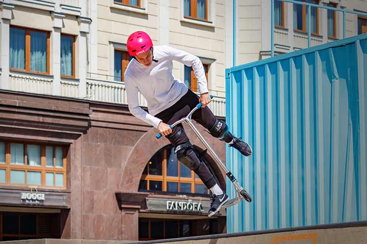Boy performing stunts using a silver scooter outside in the sunshine