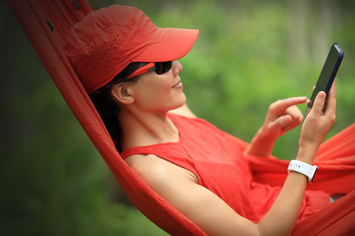Woman in led in hammock wearing a smartwatch and listening to music on her phone