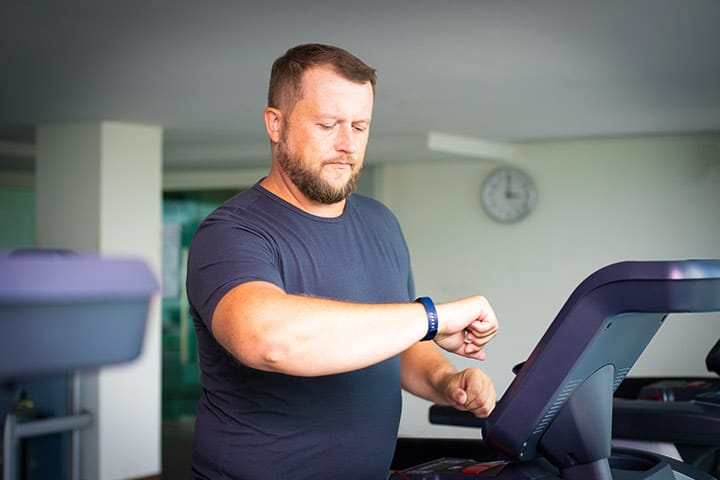A man on a treadmill checking his smartwatch