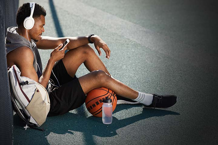 Man sat with basketball listening to music
