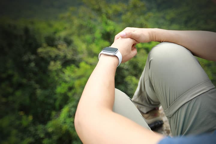 person wearing apple watch in nature