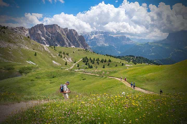 People trekking through fields below mountains