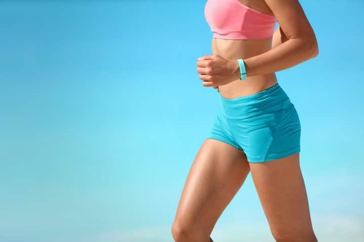 Running woman wearing a fitness tracker