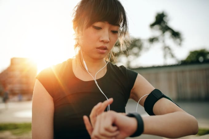 Women exercising and checking her heart rate on a smartwatch.