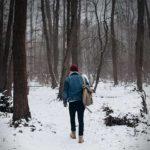 Man walking through snow covered woods