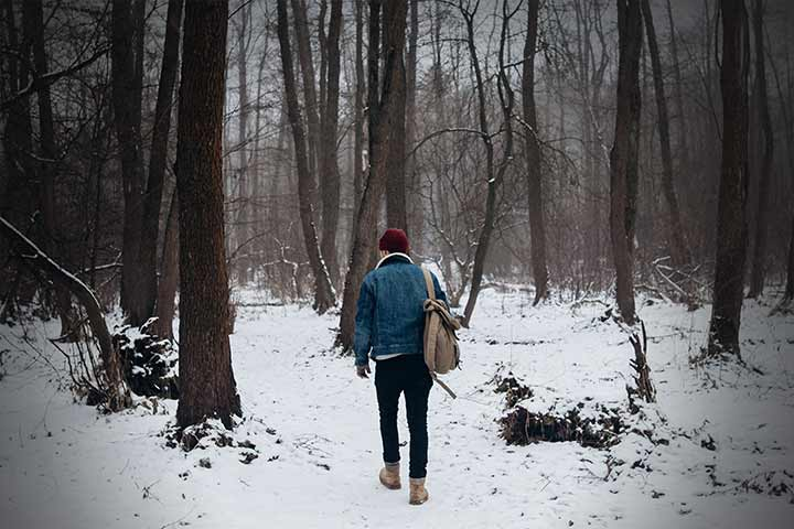 Man walking through snow covered woods