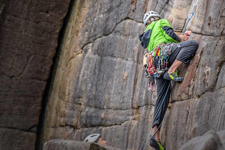 Female rock climbing and being spotted by male partner