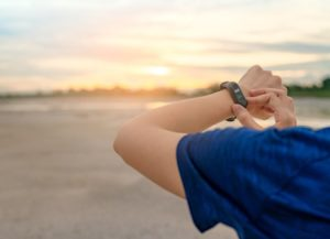 Person checking fitness on smartwatch in sunset