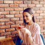 woman drinking coffee wearing pink smartwatch
