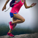 Woman running in pink and blue activewear