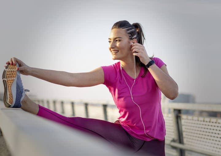 Woman wearing a smartphone and stretching after an excercise