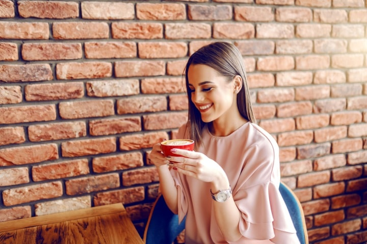 Woman drinking coffee wearing pink smartwatch.