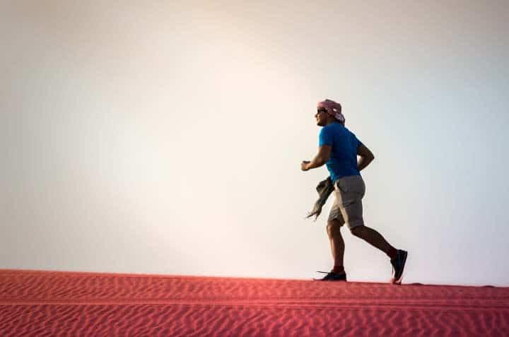 A man running up a steep sand hill