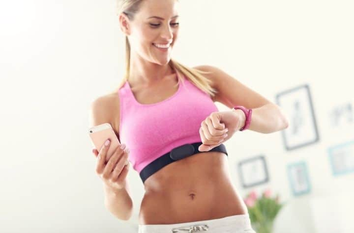 sports woman checking fitbit luxe or charge 4 fitness tracker