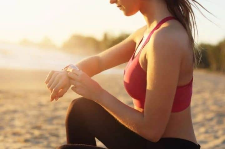 woman sat on beach at sunset checking wyze watch
