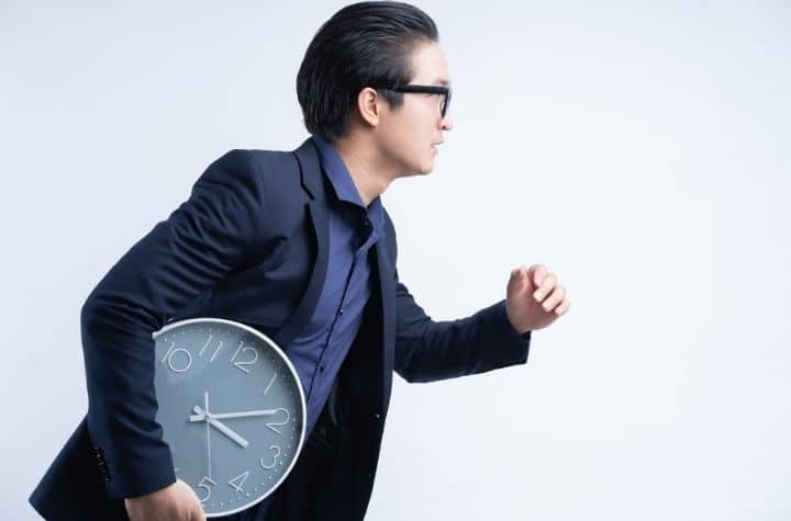 businessman running late carrying clock instead of vibrating alarm watches