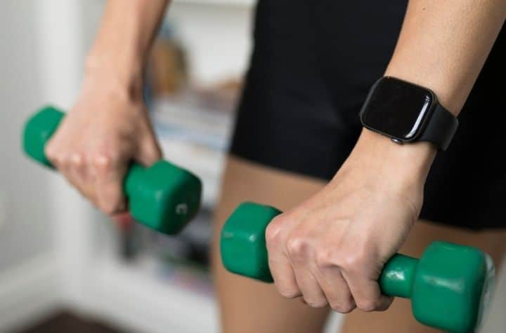 Woman lifting hand weights wearing Mobvoi's TicWatch GTH!