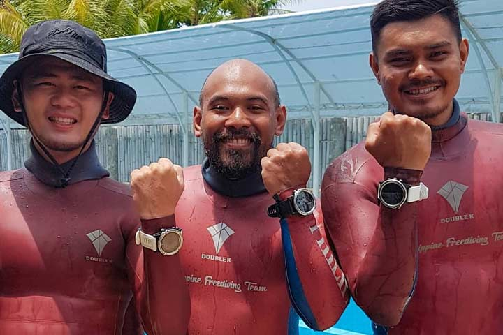 Freedivers pose with their Garmin Descent Mk1 after pool competition