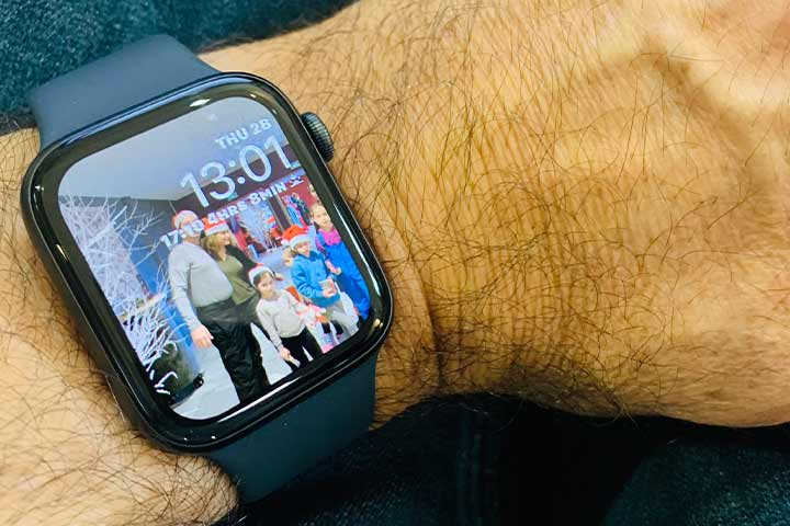Person's hand wearing smartwatch with  photo of a family on the screen