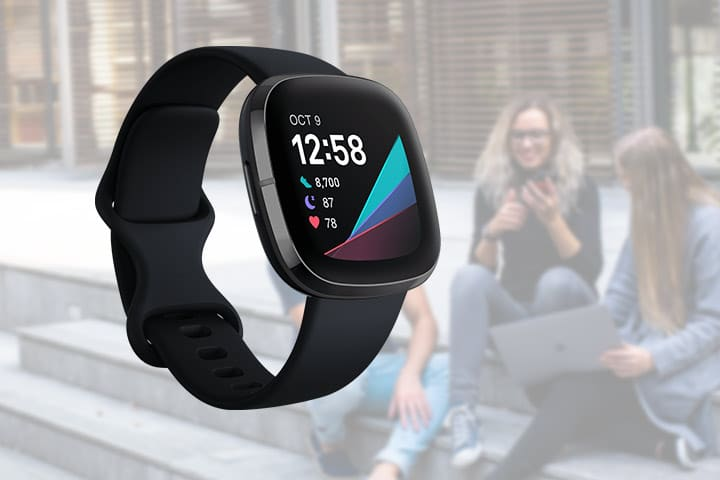 Fitbit Sense smartwatch with three people blurred in the background