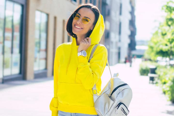 girl wearing yellow hoodie and bringing small backpack with white smartwatch