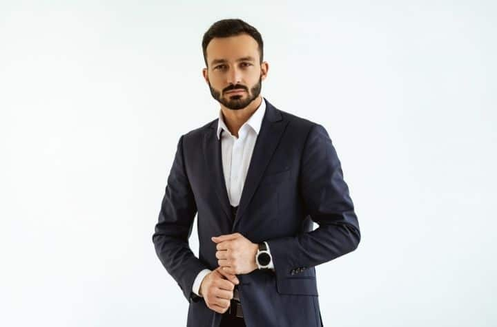businessman in suit posing with designer watches for men