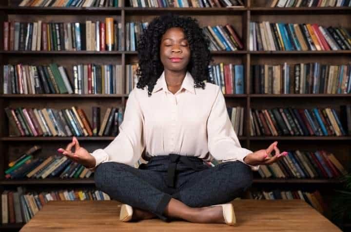 Woman sat on desk meditating using stress monitoring watches