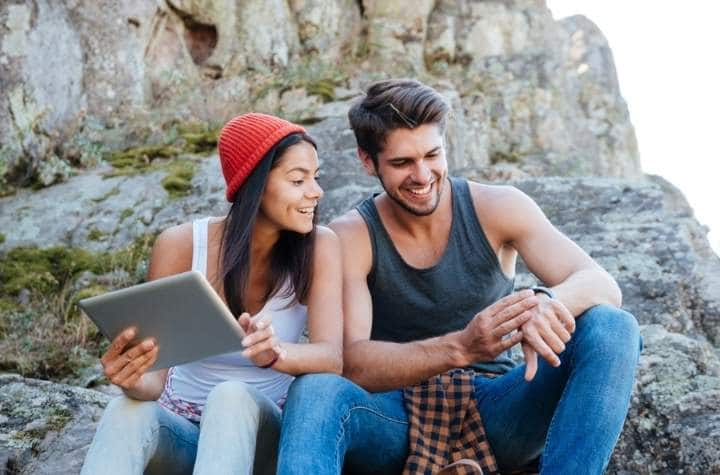 young couple outdoors looking at watches with maps