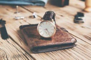 Bauhaus watch resting on brown wallet on desk